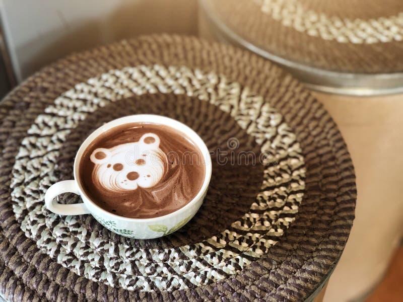 Cacau bonito da arte do latte da cara do urso no copo branco na tabela da caixa de papel fotografia de stock