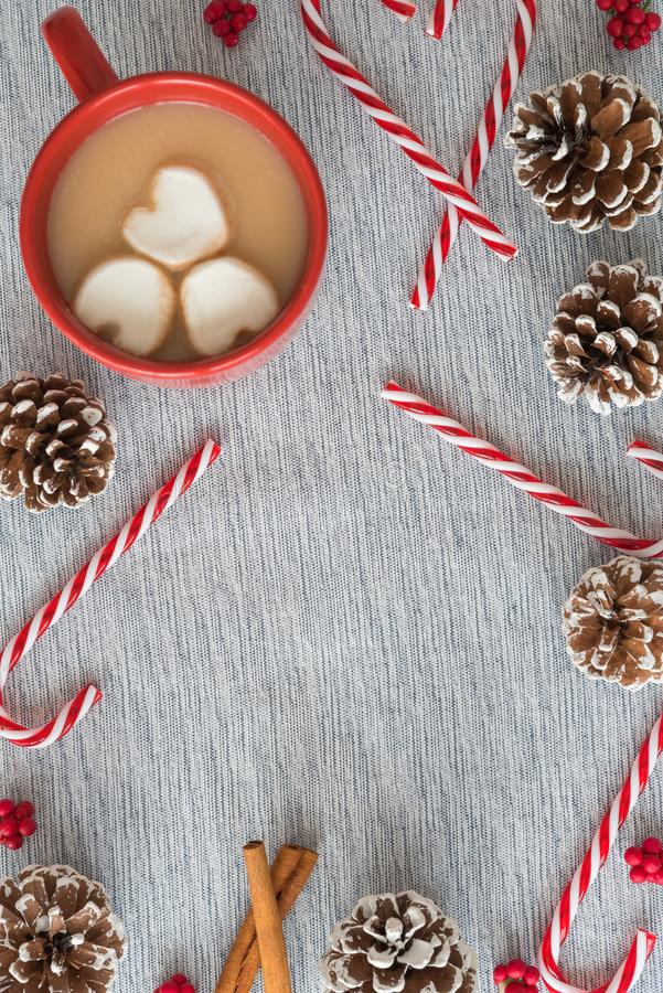 Cacau quente com marshmallows, bastões de doces, e configuração lisa do Natal dos pinecones foto de stock
