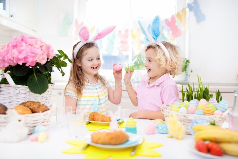 Caccia dell'uovo di Pasqua Bambini con le orecchie ed il canestro del coniglietto immagine stock libera da diritti