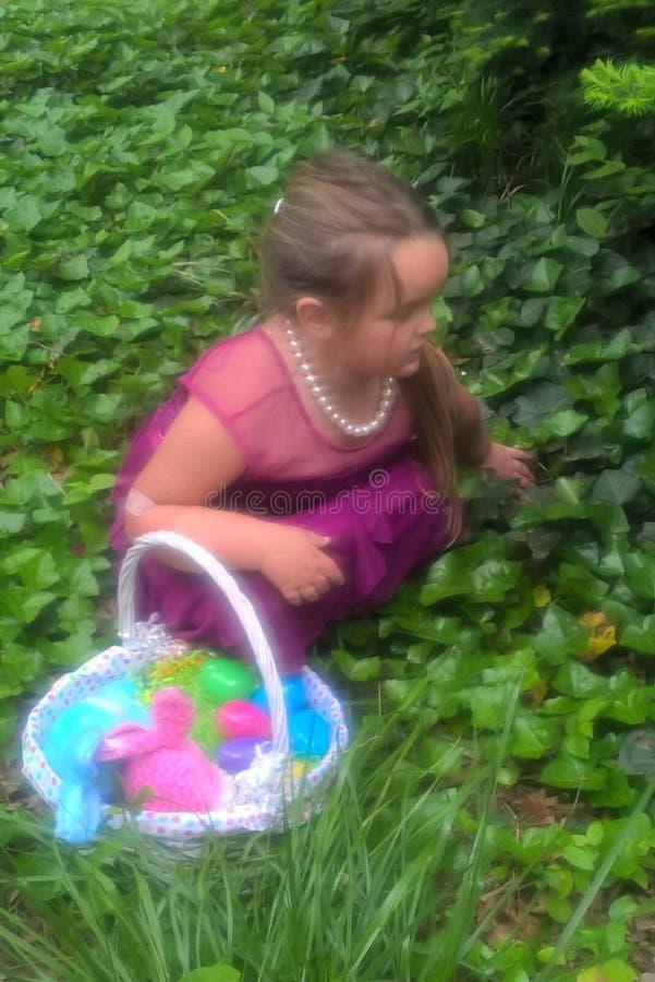 Caccia dell'uovo di Pasqua del ` s della bambina immagine stock