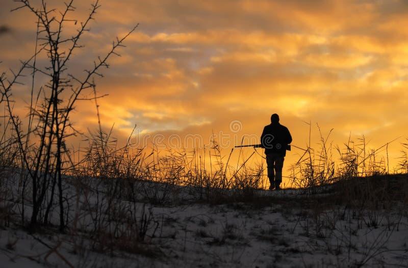 Caccia di inverno all'alba Cacciatore che si muove con il fucile da caccia fotografie stock libere da diritti