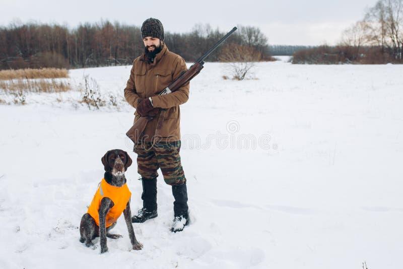 Cacciatore allegro che esamina il suo cane all'aperto fotografia stock libera da diritti