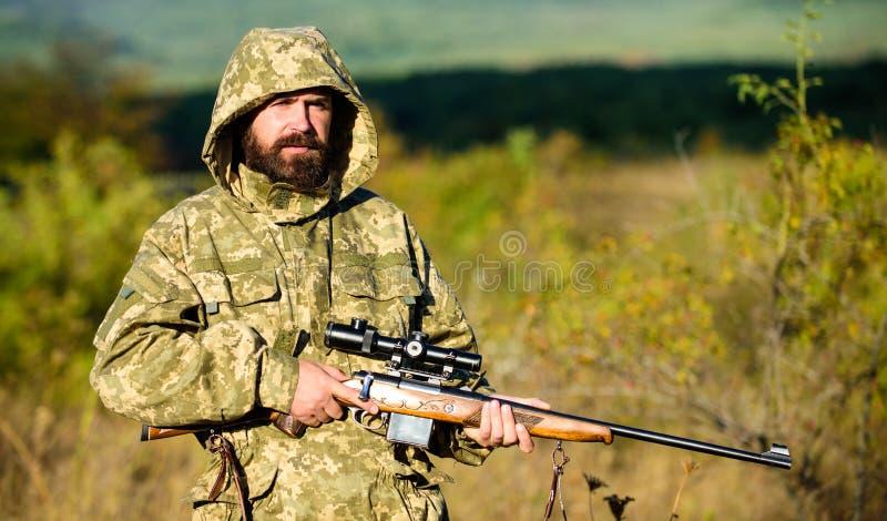 Cacciatore barbuto dell'uomo con il fondo della natura del fucile L'esperienza e la pratica presta la caccia di successo In come  fotografia stock libera da diritti
