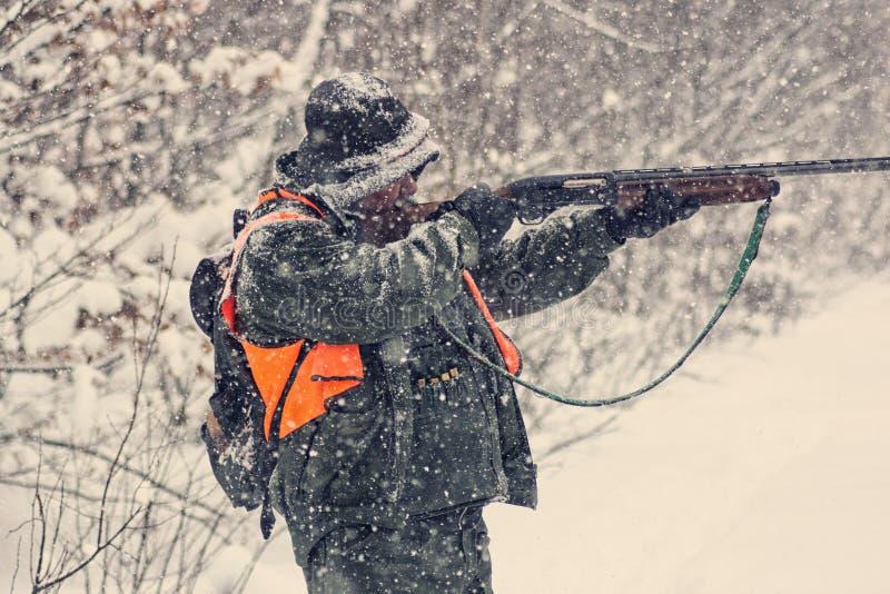 Cacciatore in cammuffamento con il fucile da caccia sulla caccia di inverno fotografia stock