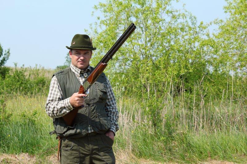 Cacciatore che propone con il fucile da caccia fotografia stock libera da diritti