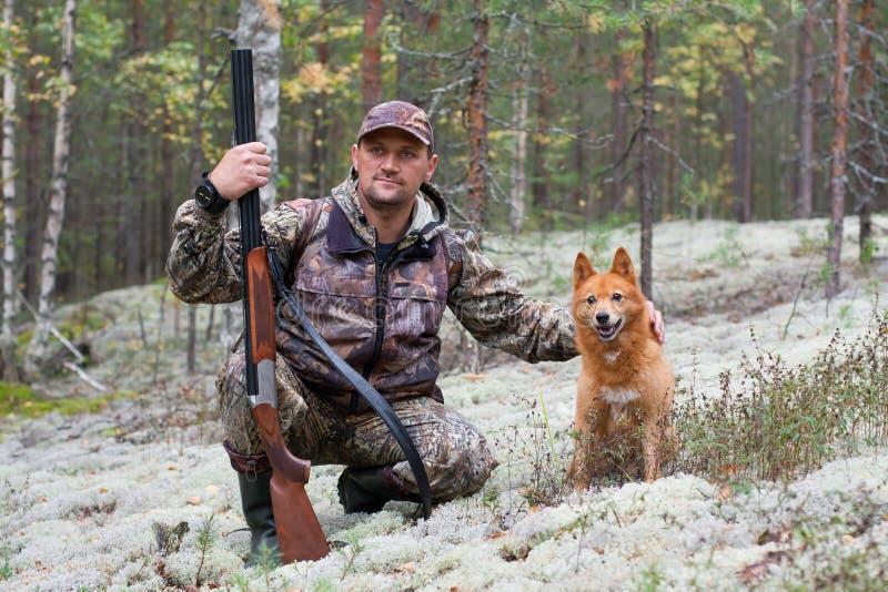 Cacciatore che segna il suo cane fotografia stock