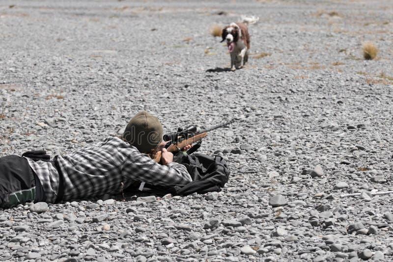 Cacciatore con il fucile ed il cane da caccia fotografia stock