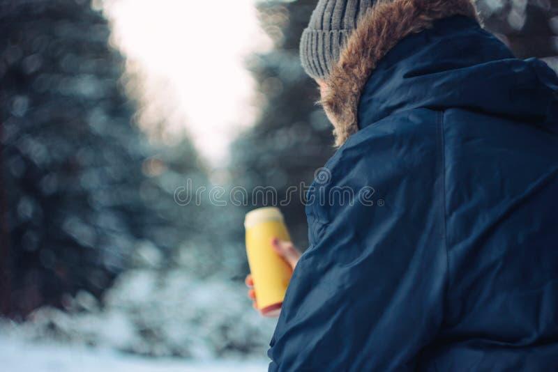 Cacciatore del silvicoltore del viaggiatore dell'uomo nella foresta di inverno che si siede sull'albero caduto immagine stock