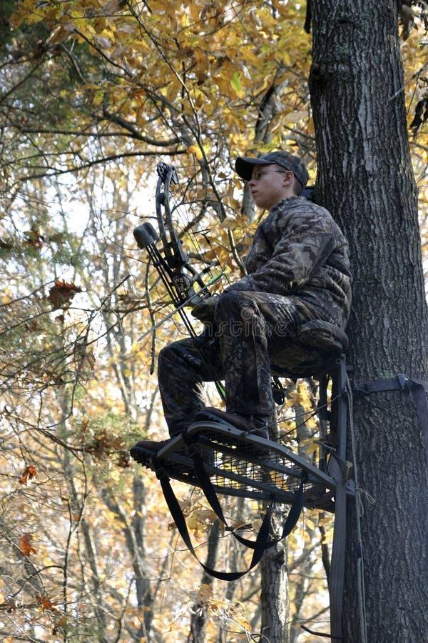Cacciatore dell'arco che attende nel basamento dell'albero fotografia stock libera da diritti