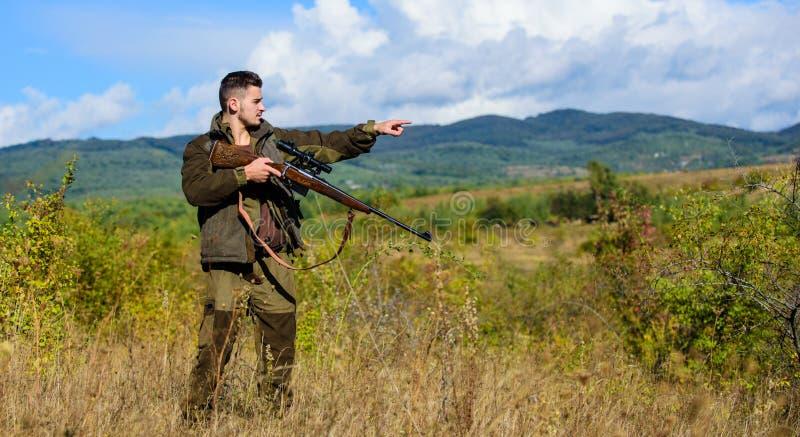 Cacciatore dell'uomo che tende il fondo della natura del fucile L'esperienza e la pratica presta la caccia di successo Ambiente d immagine stock