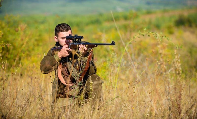 Cacciatore dell'uomo che tende il fondo della natura del fucile L'esperienza e la pratica presta la caccia di successo Ambiente d fotografia stock