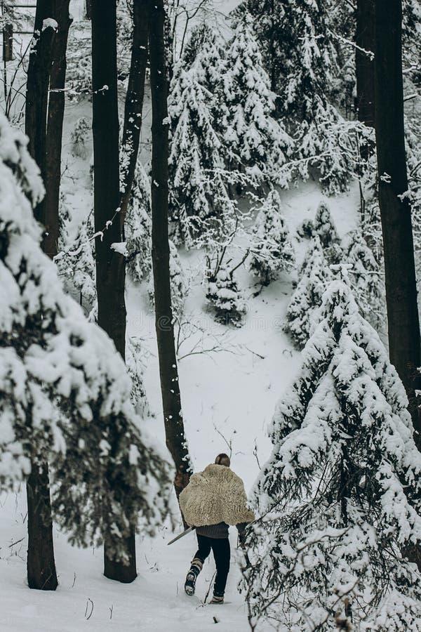 Cacciatore di Viking in cuoio che cammina nella foresta di inverno della neve con acciaio a immagine stock