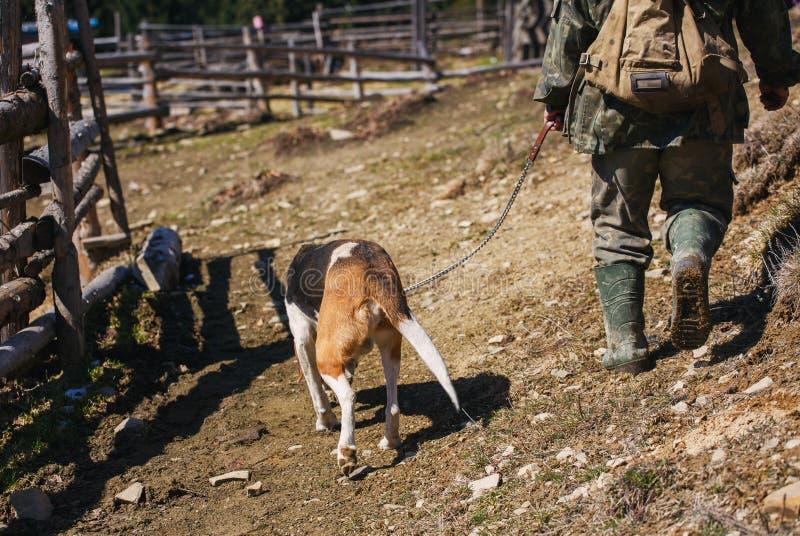 Cacciatore ed il suo cane che vanno sulla strada non asfaltata immagini stock