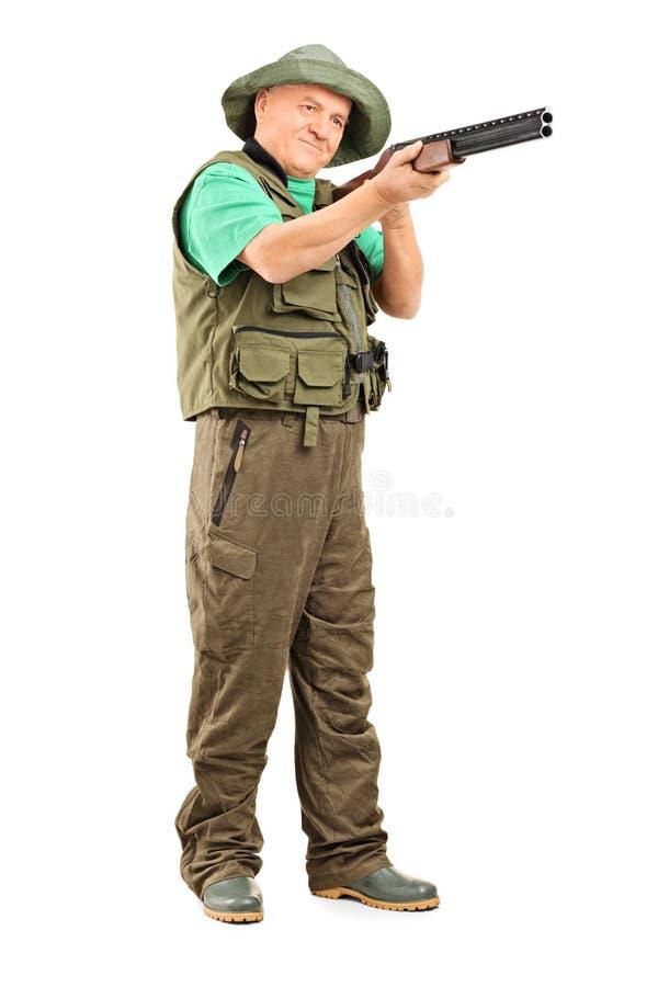 Cacciatore maturo che tende con un fucile da caccia fotografie stock