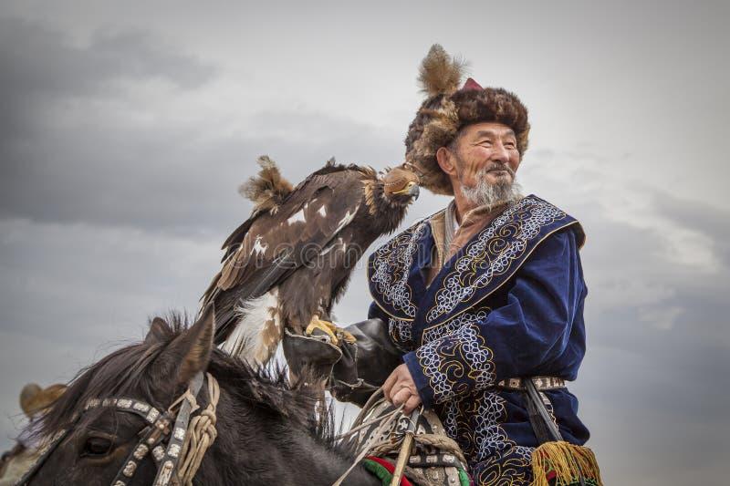 Cacciatore mongolo dell'aquila del nomade sul suo cavallo immagini stock