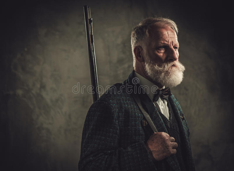 Cacciatore senior con un fucile da caccia in un abbigliamento tradizionale della fucilazione, posante su un fondo scuro fotografie stock libere da diritti
