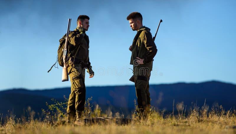 Cacciatori barbuti degli uomini con il fondo della natura del fucile L'esperienza e la pratica presta la caccia di successo In co fotografia stock