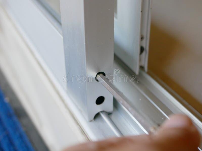 Cacciavite in mano di un uomo che regola i rulli di porta di vetro di scivolamento immagine stock