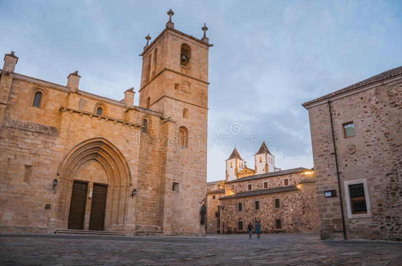 Cobblestone square with gothic church, buildings and people at dusk in Caceres royalty free stock photo