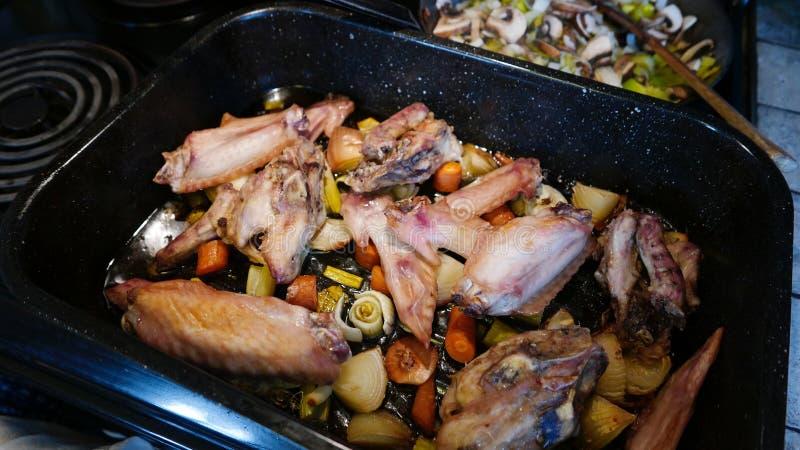 Cacerola de alas de pavo y de mirepoix asados con las setas y los puerros que cocinan en la parte posterior de la estufa fotos de archivo