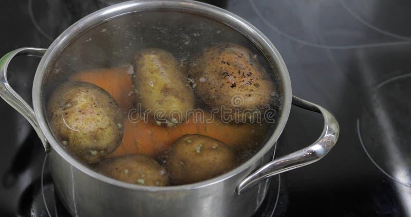 Cacerola de ebullici?n caliente con las patatas y las zanahorias de las verduras El cocinar en cocina fotos de archivo libres de regalías