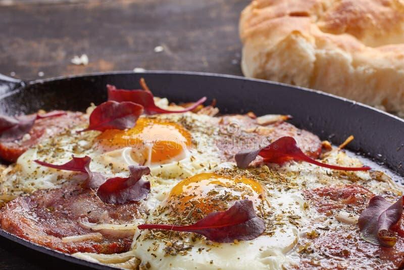 Cacerola de huevos fritos con la cebolla, el jamón y el cardo imagenes de archivo