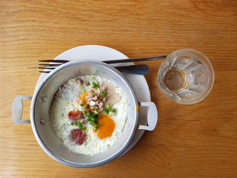 Cacerola de huevos fritos y de perejil con pan y agua potable en la tabla de madera La comida del desayuno imágenes de archivo libres de regalías