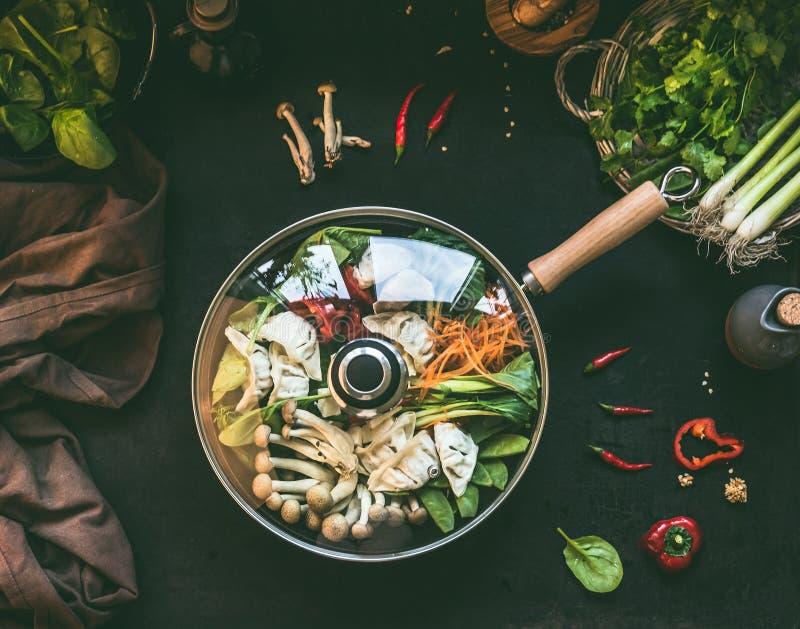 Cacerola del wok con el pote caliente coreano vegetariano con las verduras y las bolas de masa hervida en fondo rústico oscuro de fotografía de archivo libre de regalías