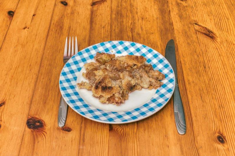 Cacerola llenada de la empanada hecha en casa de la migaja de Apple en un piso de madera de la cocina foto de archivo