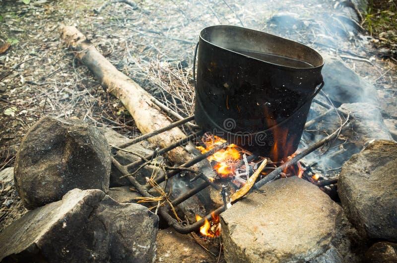 Cacerola negra vieja con el agua hirvienda en hoguera fotografía de archivo