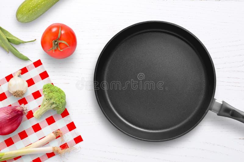 Cacerola vacía en la tabla de cocina con las verduras por otra parte fotografía de archivo libre de regalías