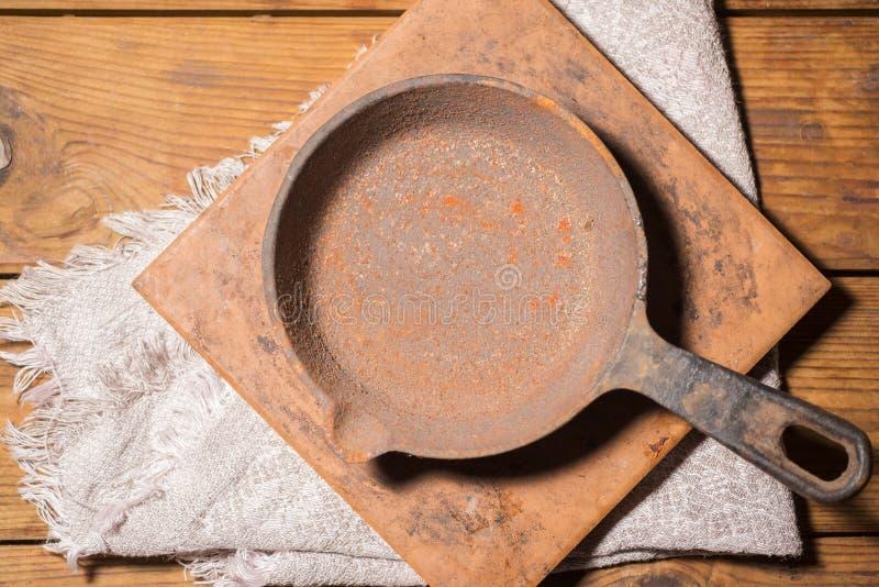 Cacerola vacía vieja del arrabio  platos oxidados imagenes de archivo