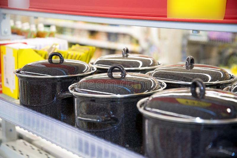 Cacerolas esmaltadas negras con la tapa en la tienda imagen de archivo