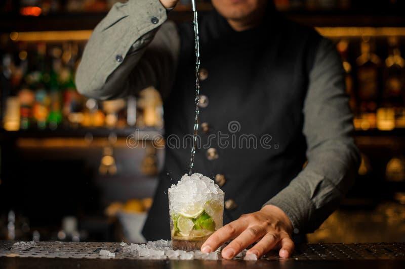 Cachaca de colada del camarero en el vidrio de cóctel Proceso del makin fotografía de archivo