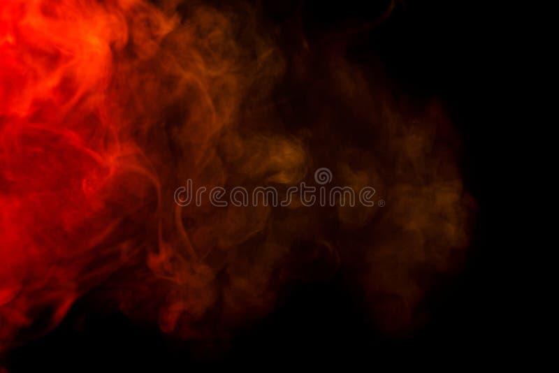Cachimbo de água vermelho e amarelo abstrato do fumo em um fundo preto imagens de stock royalty free