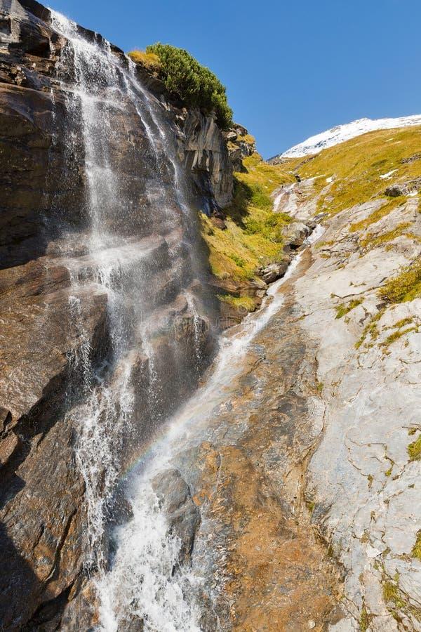 Cachoeira alpina pitoresca, estrada alpina alta de Grossglockner em cumes austríacos fotos de stock