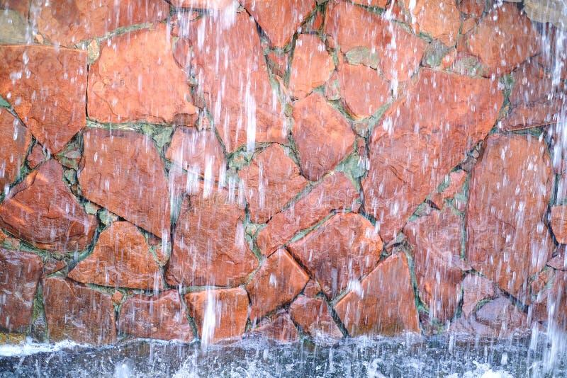 Cachoeira artificial no parque de diversões Água de fluxo no fundo da pedra vermelha natural imagens de stock