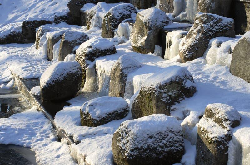Cachoeira congelada com pedregulhos cobertos de neve imagem de stock