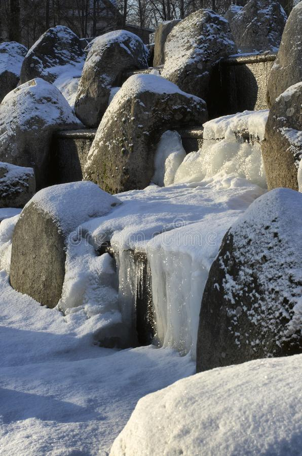 Cachoeira congelada com pedregulhos cobertos de neve fotos de stock