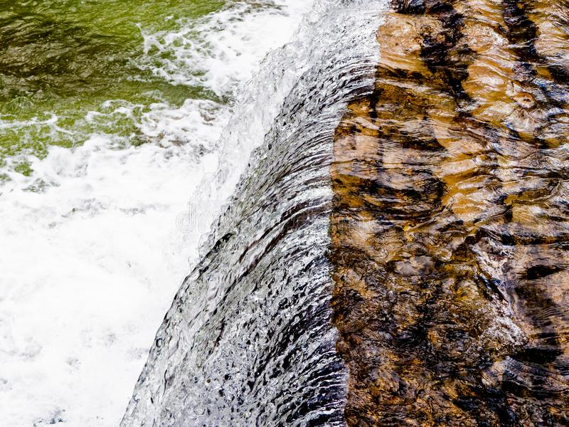 Cachoeira da corredeira da água branca que deixa de funcionar ao assoalho do rio fotografia de stock