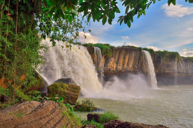 Cachoeira de Nour do Dray, contra o céu azul, entre a vegetação equatorial verde, província de Daklak, Vietname imagem de stock royalty free