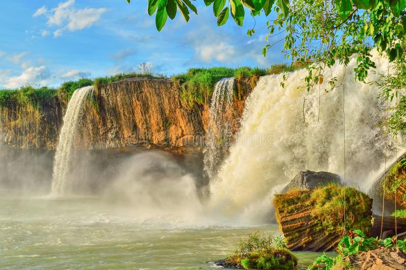 Cachoeira de Nour do Dray, contra o céu azul, entre a vegetação equatorial verde, província de Daklak, Vietname fotografia de stock royalty free