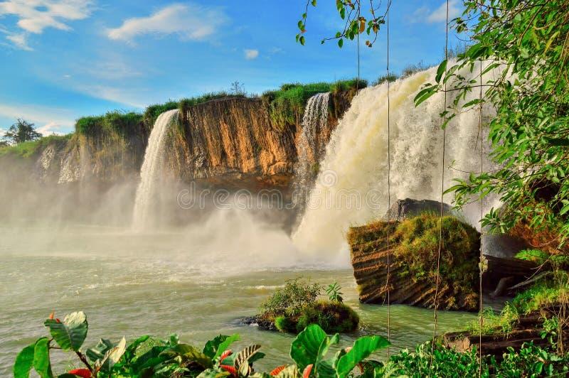Cachoeira de Nour do Dray, contra o céu azul, entre a vegetação equatorial verde, província de Daklak, Vietname fotos de stock