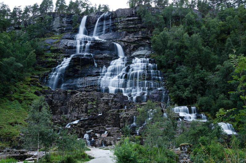 A cachoeira de Tvindefossen em Noruega fotografou na exposição longa durante o crepúsculo fotografia de stock