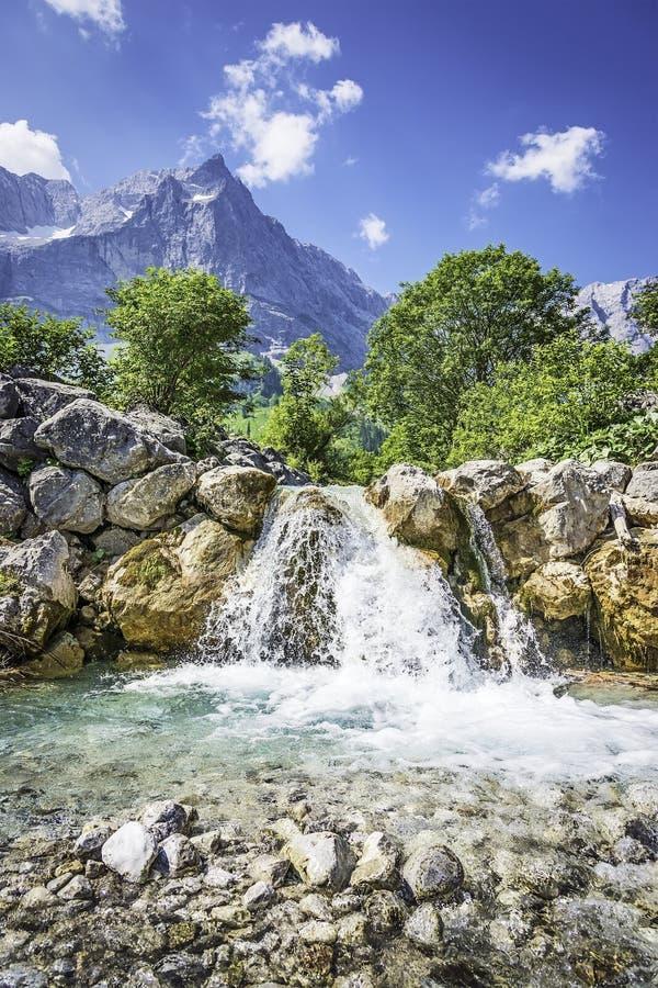 Cachoeira e rochas nos cumes austríacos imagem de stock