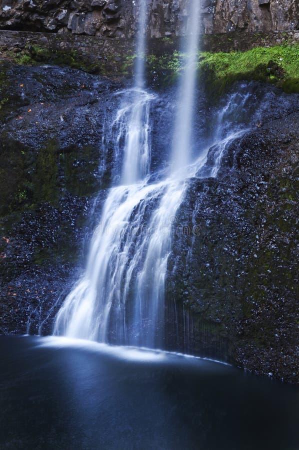 Cachoeira estratificado bonita que conecta sobre rochas com um refection azul etéreo macio do tom na água fotos de stock royalty free