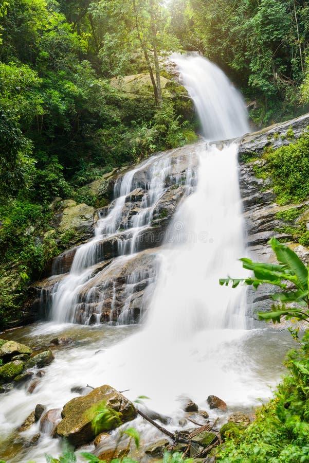 Cachoeira na floresta tropical com o alargamento da luz do sol no wate de Mae Pan foto de stock royalty free