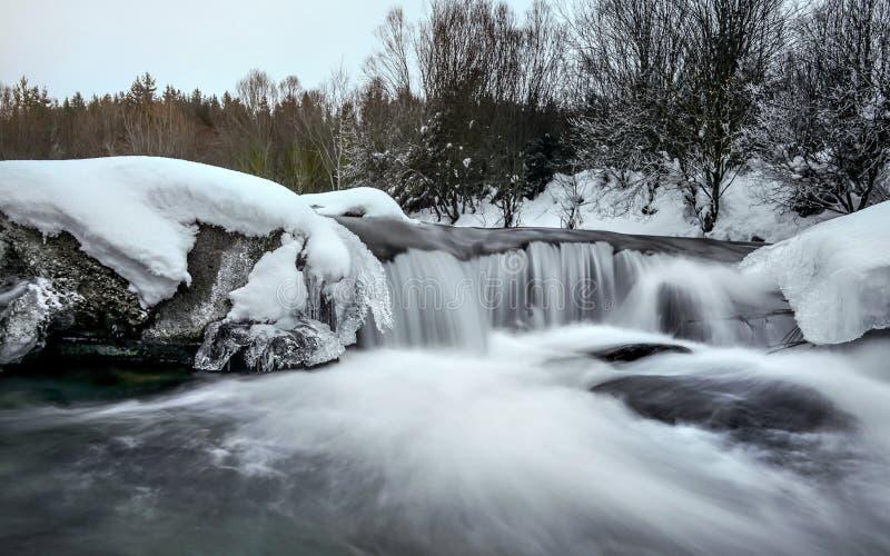 A cachoeira pequena no rio no inverno, exposição longa faz a água liso leitoso, a neve e o gelo ao redor, estabelecer-se do sol d fotografia de stock