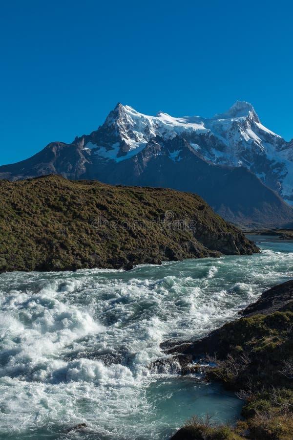 Cachoeira que conecta com um rugido tempestuoso com uma cordilheira no fundo, Torres del Paine, parque nacional, o Chile fotos de stock royalty free