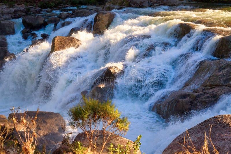 Cachoeira que conecta sobre as rochas, últimos raios de luz de travamento foto de stock